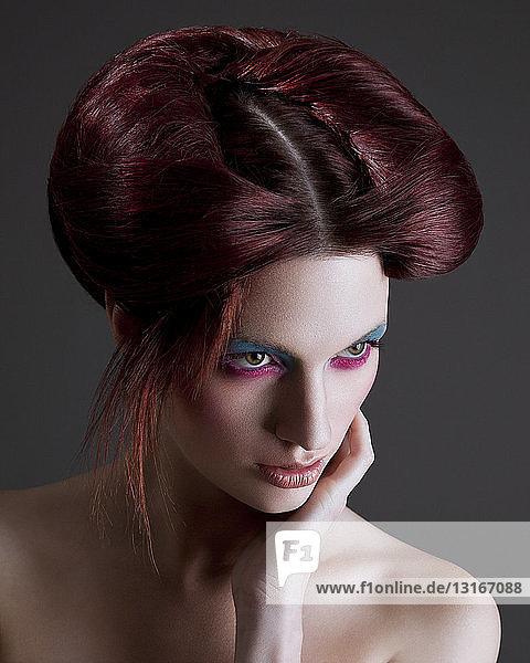 Porträt einer jungen Frau mit schwerem Augen-Make-up und gestyltem Haar