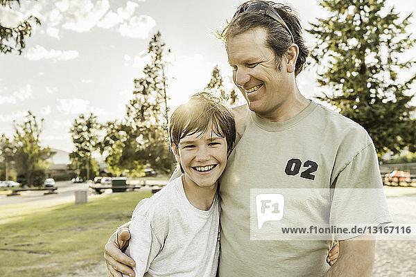 Vater und jugendlicher Sohn lächeln