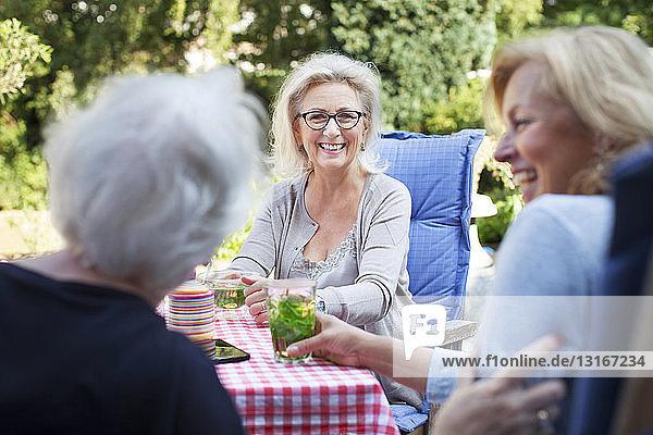 Drei Frauen sitzen im Garten und genießen ein Getränk