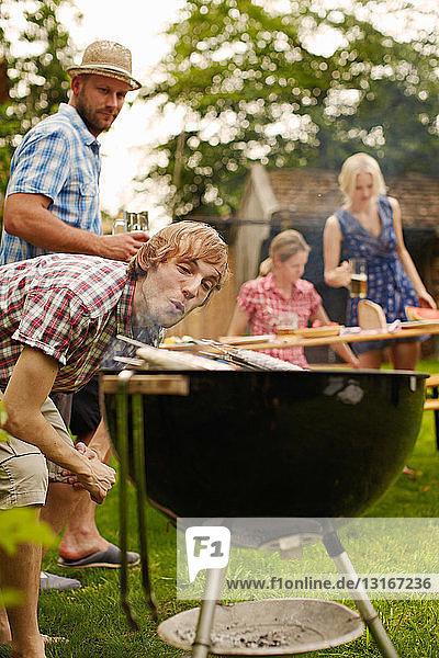 Mann grillt Fisch auf dem Barbecue im Freien