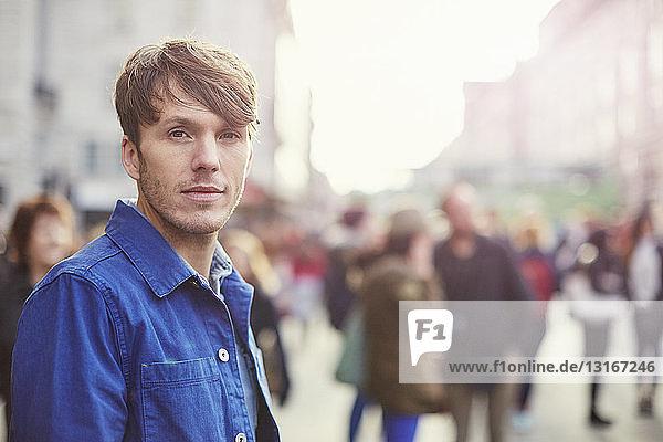 Portrait of mid adult man on crowded street  London  UK