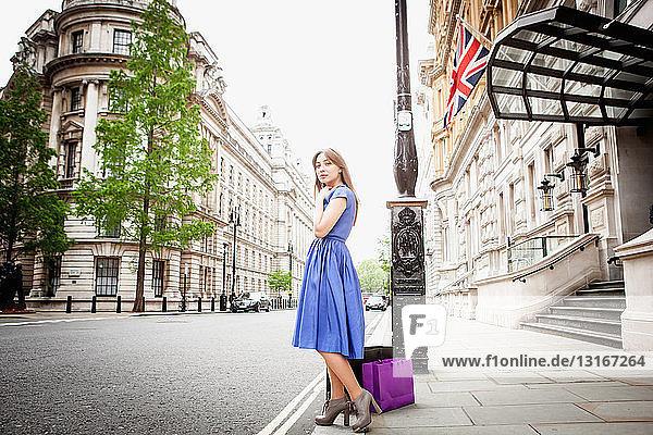 Junge Frau steht mit Einkaufstaschen auf Londoner Straße