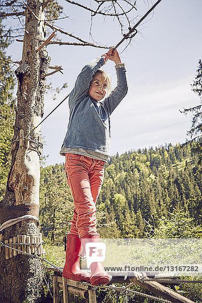 Junges Mädchen geht über eine Einseilbrücke