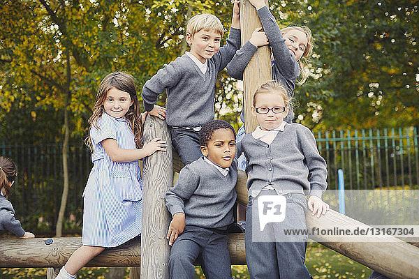Portrait of elementary schoolchildren on playground climbing frame