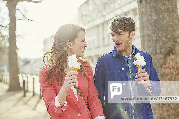 Couple eating ice cream cones whilst strolling along street  London  UK