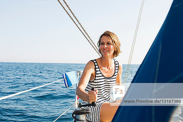 Woman pulling rigging on boat