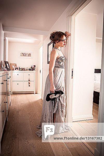 Müde junge Frau im Abendkleid  hält Schuhe im Flur