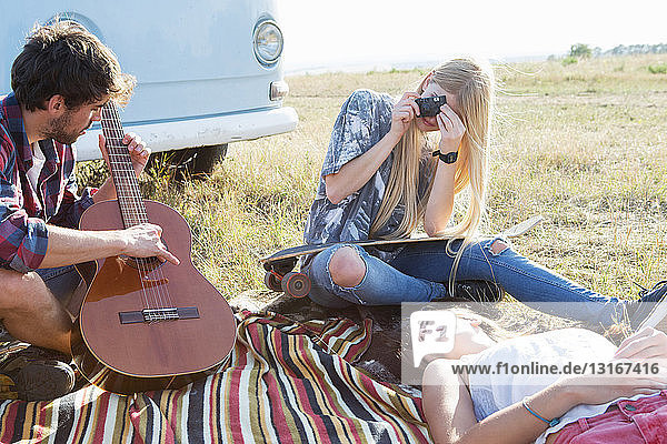 Junger Mann spielt Gitarre  junge Frauen hören zu
