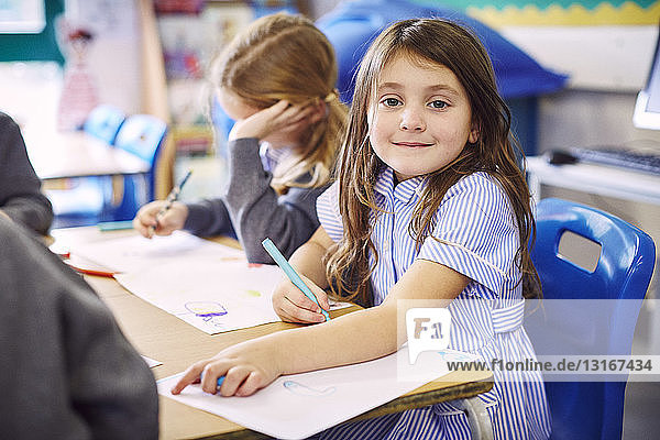 Portrait of girl drawing at desk in elementary school