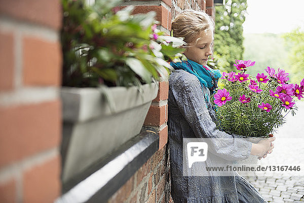 Portrait of girl leaning against wall with flower pot plant in garden
