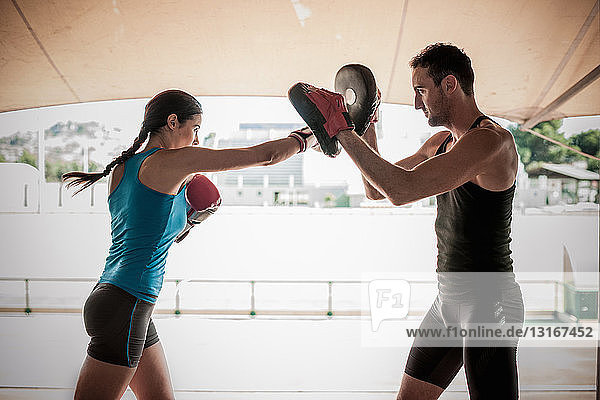 Junge Frau boxt mit Personal Trainer