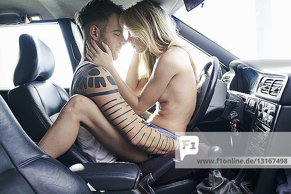 Partially clothed young woman straddling young man in car