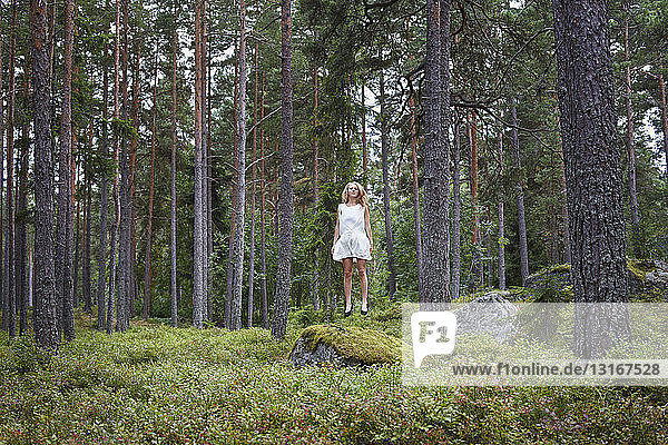 Teenage girl jumping in forest