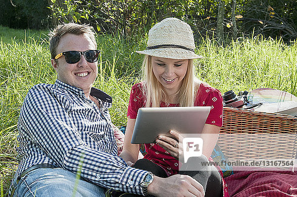 Young couple sitting on picnic blanket using digital tablet