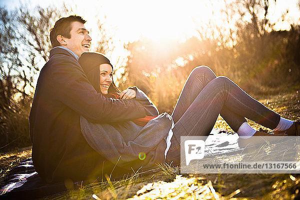 Paar sitzt auf einer Picknickdecke und umarmt sich