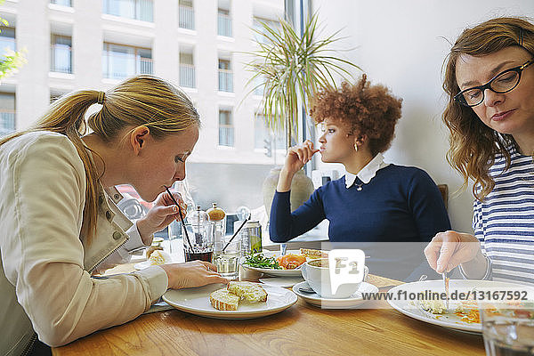 Three women eating salad lunch in cafe