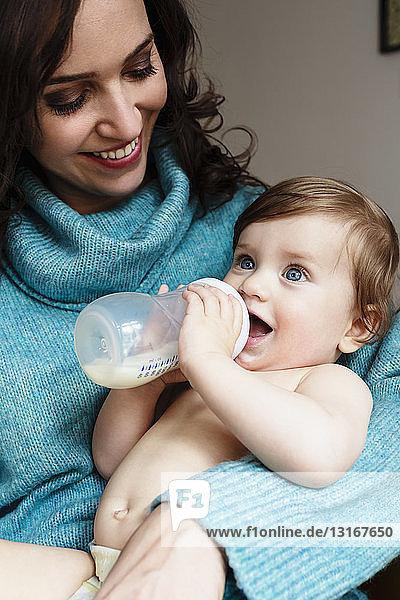 Mutter beobachtet Baby Junge  der Milch aus der Flasche trinkt