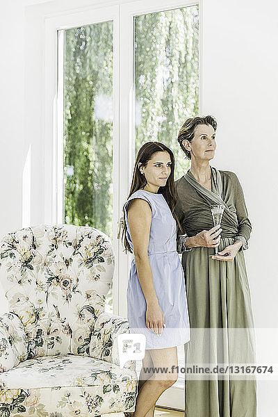 Ältere Frau und Tochter mit einem Glas Champagner im Wohnzimmer
