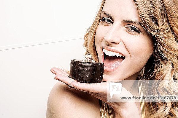 Modell hält Kuchen im Mund