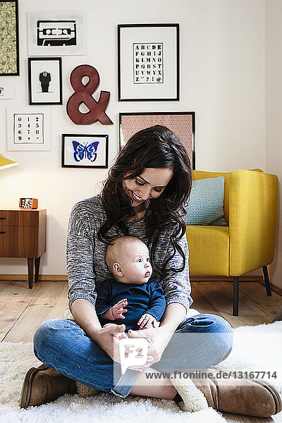 Mother and baby son sitting in living room