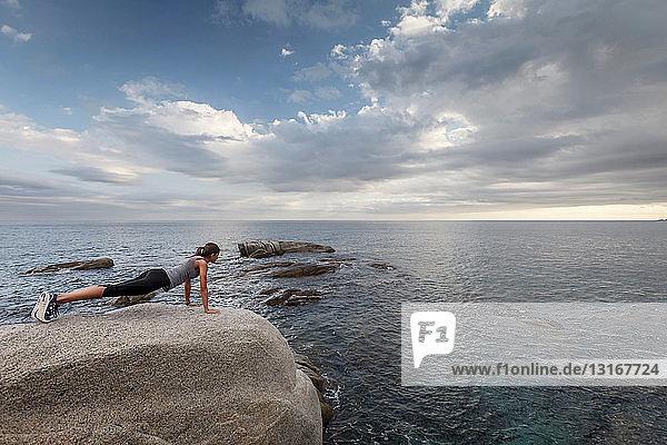 Frau auf Felsbrocken mit Blick auf den Ozean