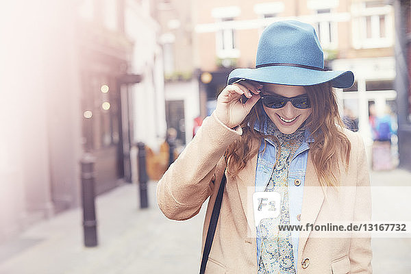 Fashionable young female shopper wearing sunglasses  London  UK