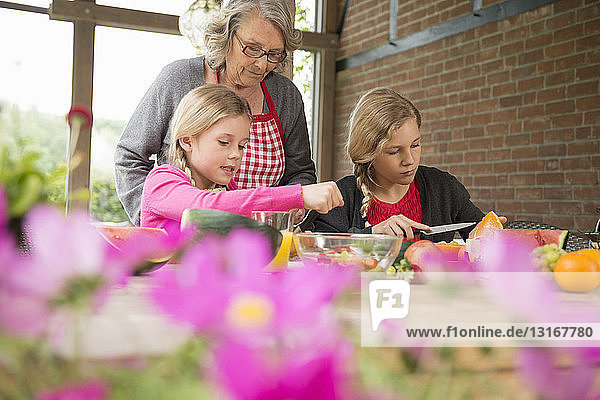 Two sisters and grandmother at kitchen table learning to slice fresh fruit