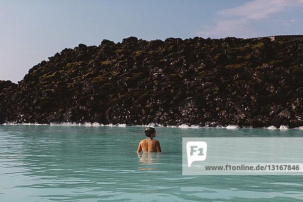 Rückansicht einer mittelgroßen erwachsenen Frau  die mit der Taille tief im Wasser steckt  Heiße Quellen in der Blauen Lagune  Island