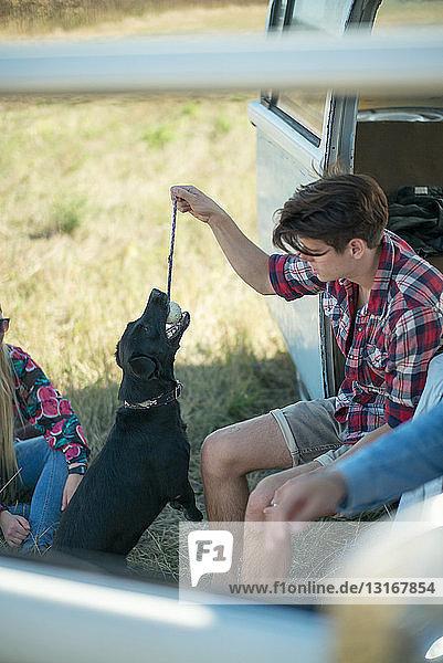 Junger Mann spielt mit Hund