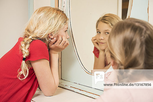 Girl staring at sister in bedroom mirror