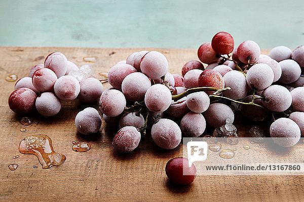 Gefrorene rote Trauben auf Holzschneidebrett