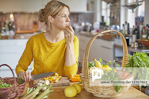Reife Frau sitzt am Küchentisch und schneidet Gemüse
