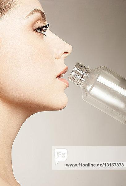 Frau trinkt aus der Flasche