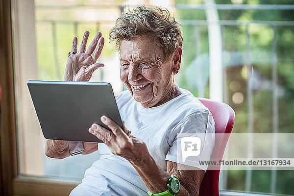 Eine sehr ältere Frau benutzt ein digitales Tablett auf dem Balkon ihrer Wohnung