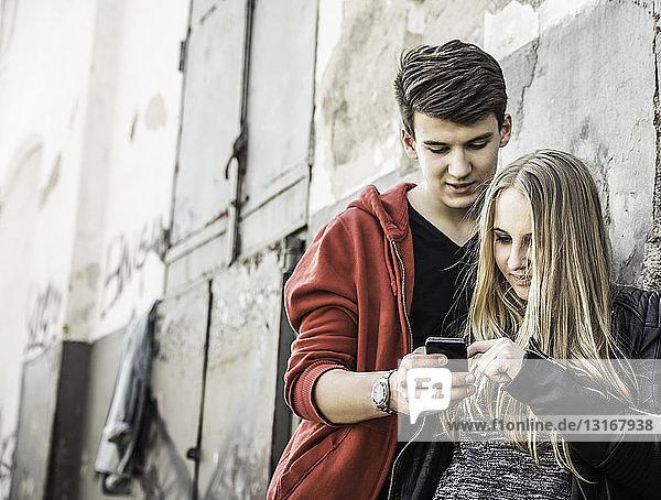Teenager-Paar nutzt Smartphone an verlassenem Gebäude