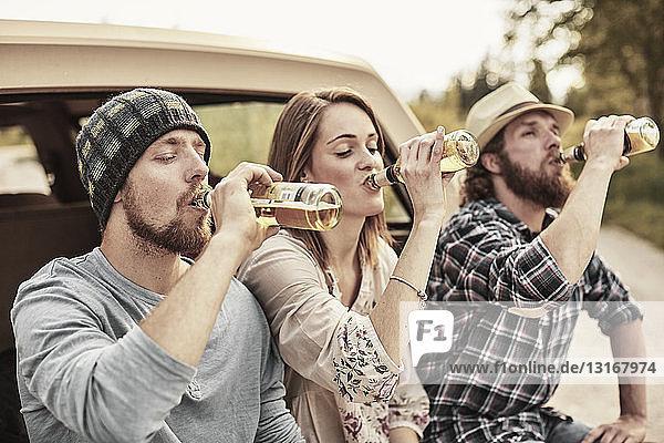 Drei Personen trinken gemeinsam Flaschenbier
