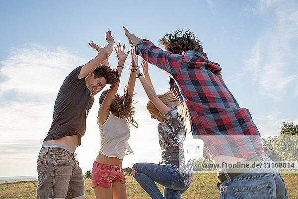 Vier Freunde springen mit erhobenen Armen