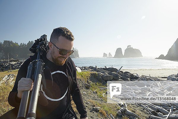 Male photographer carrying tripod on coast  Puget Sound  Washington State  USA