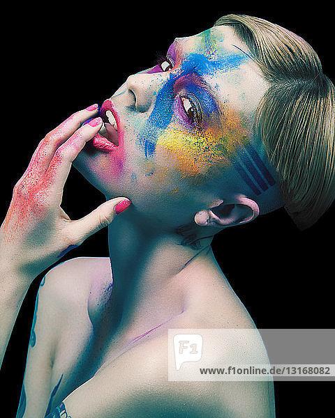 Junge Frau  nackt  berührendes Gesicht  bunter Puder und Farbe im Gesicht