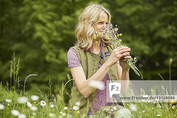 Reife Frau im Garten  Blumen riechend