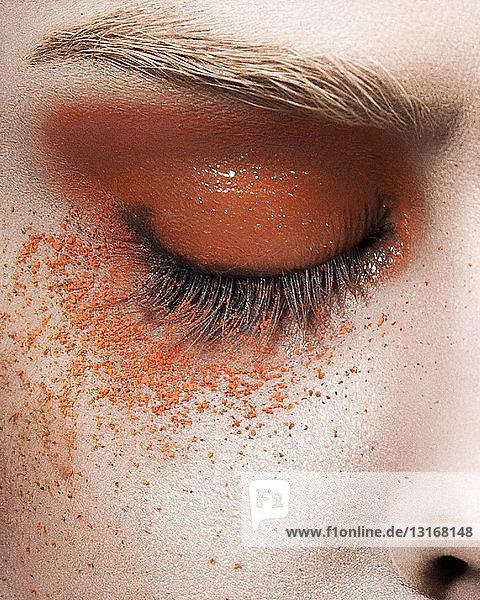 Junge Frau mit orangefarbenem Augen-Make-up  Nahaufnahme des Auges