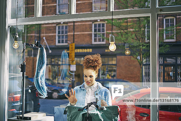 View through glass of young woman looking in shop window