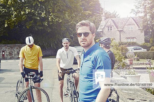 Radfahrer halten an Steinmauer  Cotswolds  UK