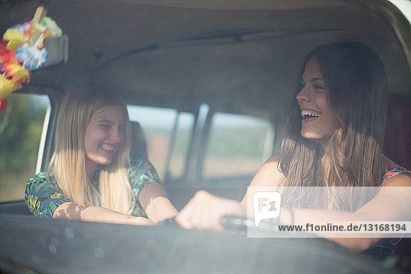 Zwei junge Frauen im Wohnmobil  lachend