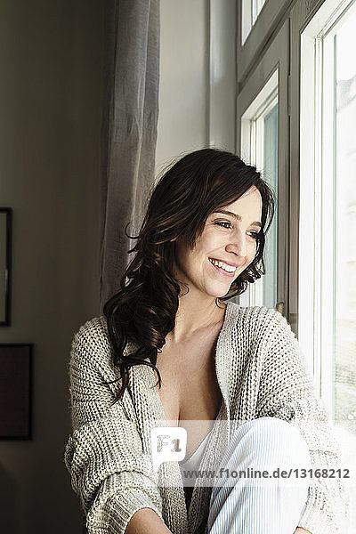 Brünette Frau am Fenster sitzend
