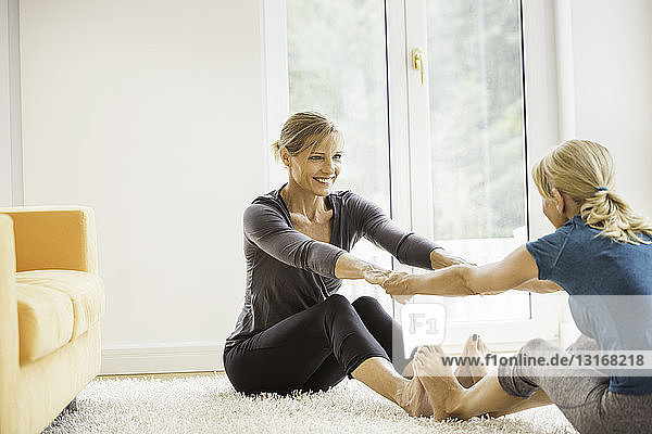 Two mature women exercising together on living room floor