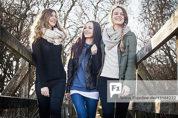 Drei Freundinnen schlendern über den Steg