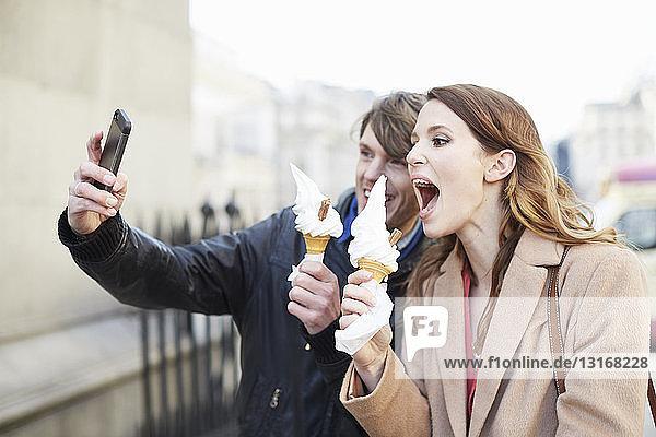 Paar mit Eiswaffeln nimmt Smartphone-Selfie  London  UK