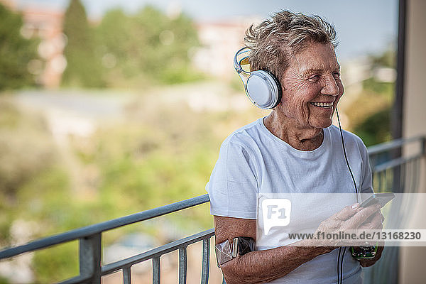A very senior woman listening to music on headphones on apartment balcony