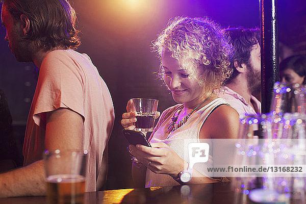 Junge Frau benutzt Smartphone im Club